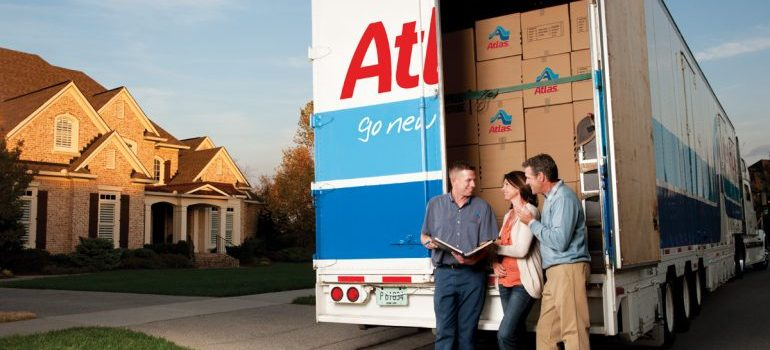 one of the best moving companies Hudson County NJ has to offer with clients in front of the truck