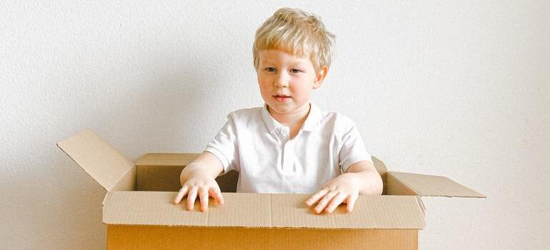 A boy playing with leftover moving boxes