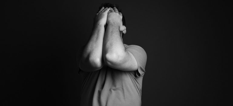 a man holding his head before overcoming moving anxiety