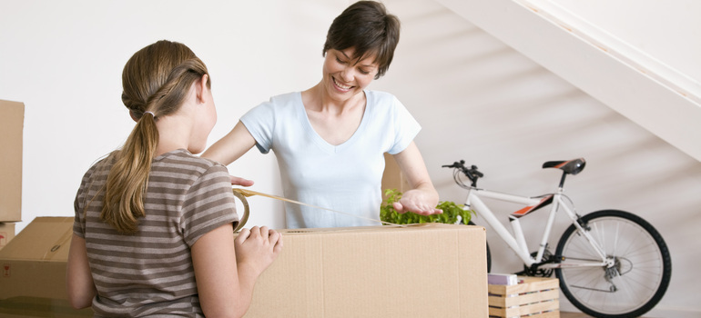 A woman and a girl holding a moving box