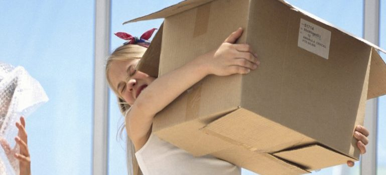 a girl carrying moving box