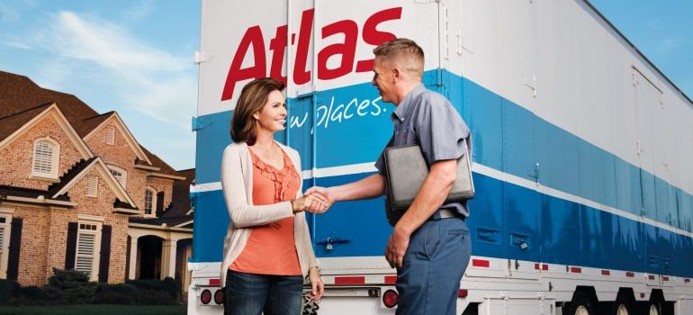 A man and a woman shaking hands in front of a moving van.