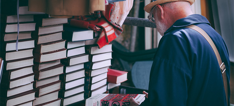 An older gentelman looking at some books about decluttering tips for seniors