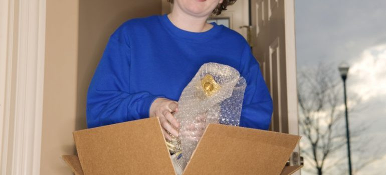 Woman wrapping her things in bubble pack to protect them from mold in storage units