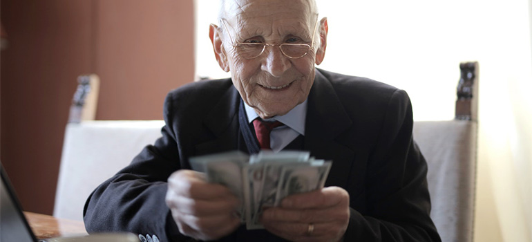 An older gentelman in a suit counting some money