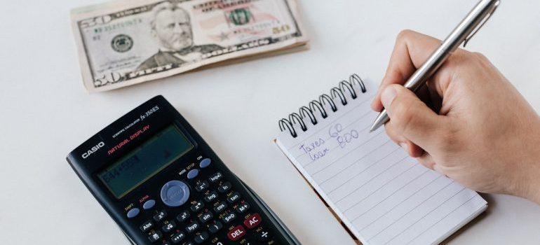 Notepad, calculator and dollar bills