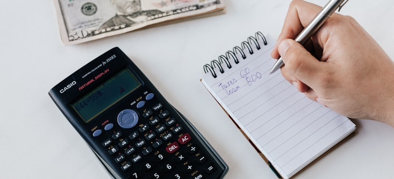 Person calculating moving rates with a calculator and a notepad.
