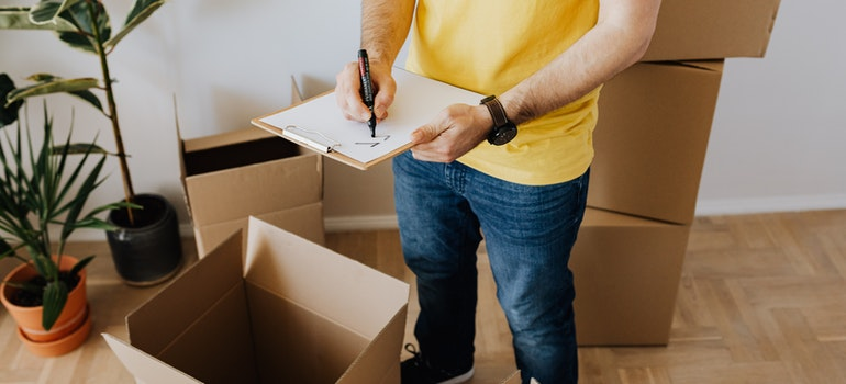 Person writing a checklist trying to find the best moving rates in NJ.