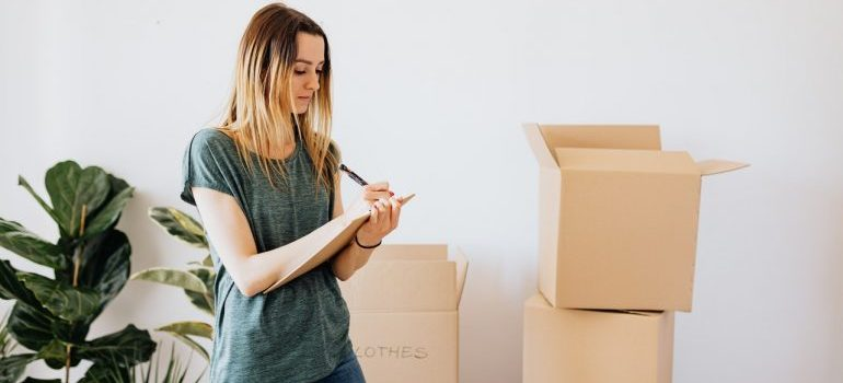Woman writing things down while packing.