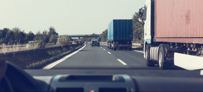 A dash-board view of a highway with trucks passing by.