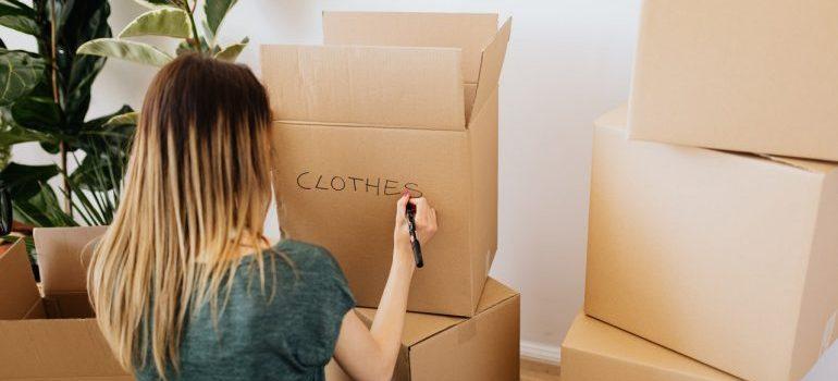 A woman labeling boxes.