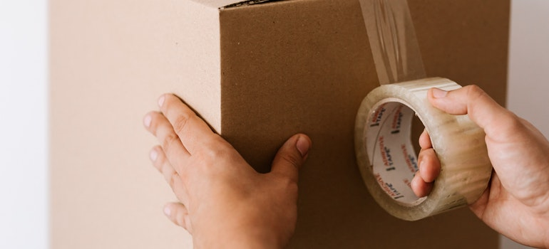 A person taping a box.