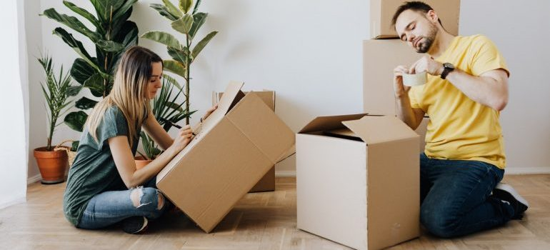 A man and woman packing boxes together.