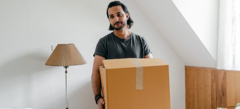 A mover carrying a box to help you maintain your sanity while moving from NY to NJ.