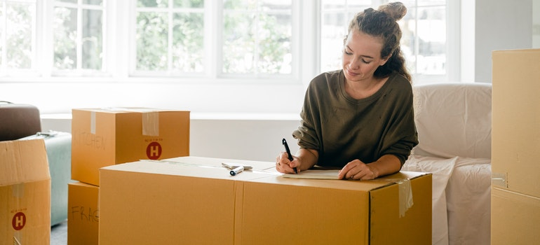 A woman writing a moving checklist on a cardboard box to prepare for moving on a deadline.
