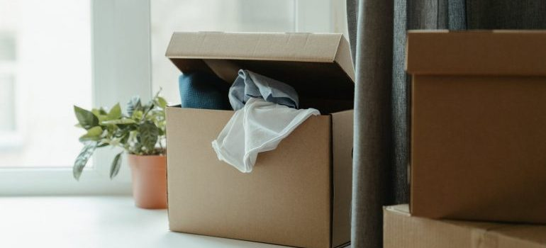A cardboard box containing clothes.