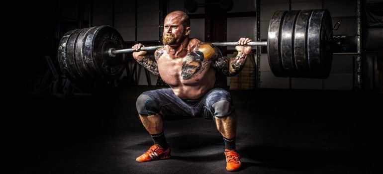 A bodybuilder representing how hard it will be if you decide poorly when choosing between hiring NJ movers vs DIY move.