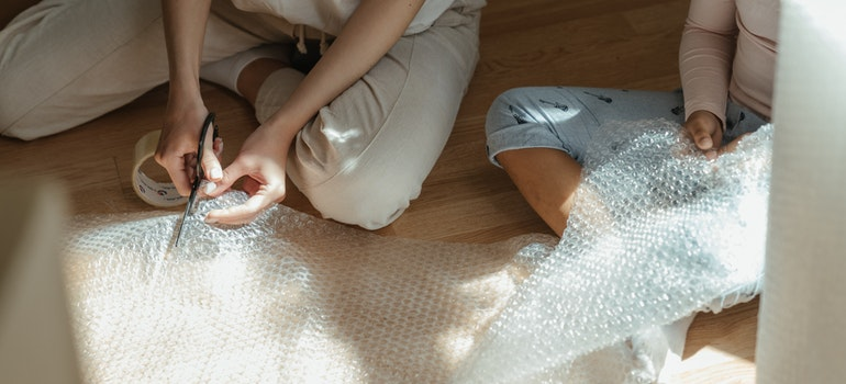 Two women cutting bubble wrap on the floor.