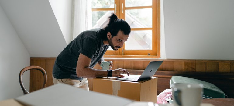 A man checking his computer while on a break from packing his electronics for a move.