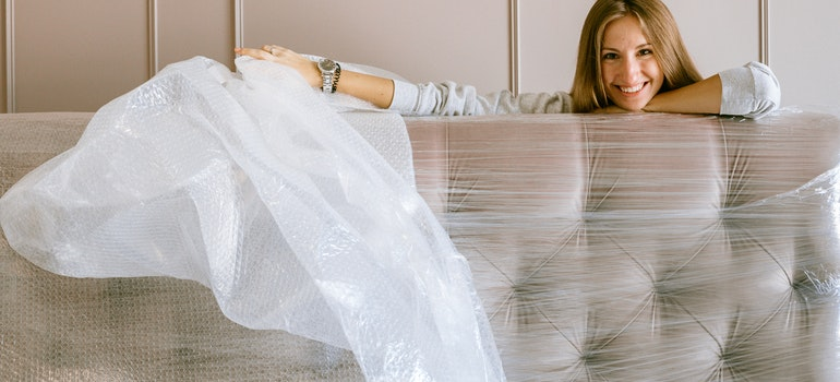 A woman wrapping her couch in plastic wrap, to protect belongings from the rain on her moving day.