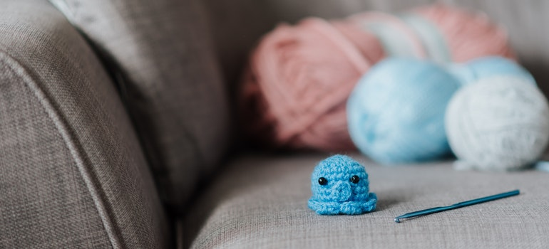 A tiny knitted octopus on a couch.