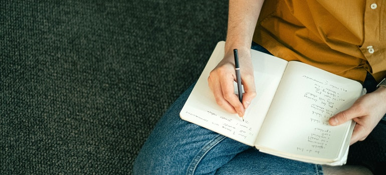 Person writing a to do list to relocate with family from NJ stress-free