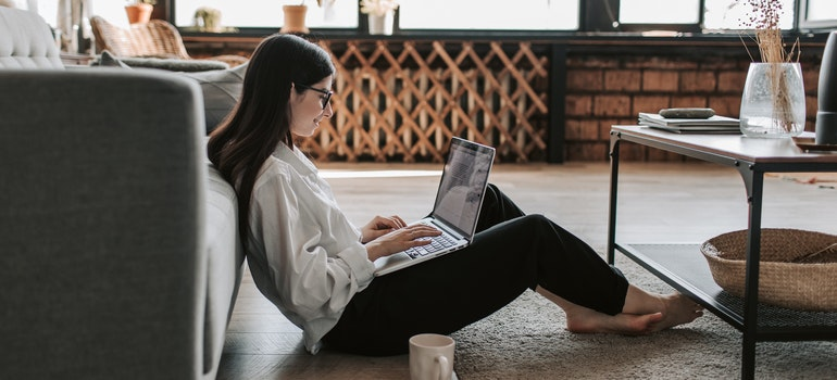 Woman sitting on the floor and researching companies before renting a moving truck