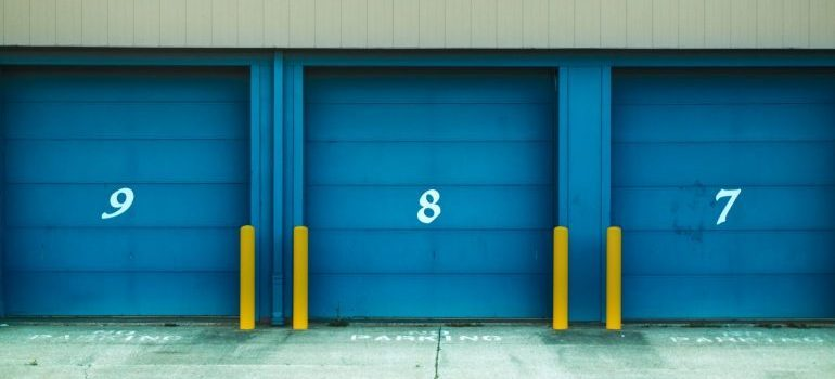 Storage facilities with blue doors and numbers on them.