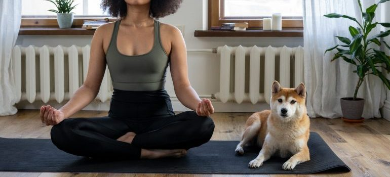 A puppy and a woman meditating together to make moving with pets easier for both of them.