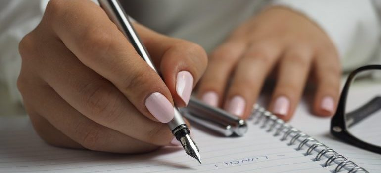A girl writing a post-moving to do list.