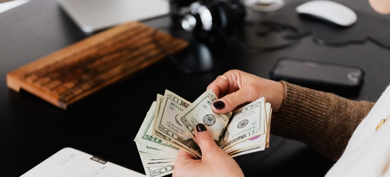 Woman counting money for bills before transferring utilities when moving