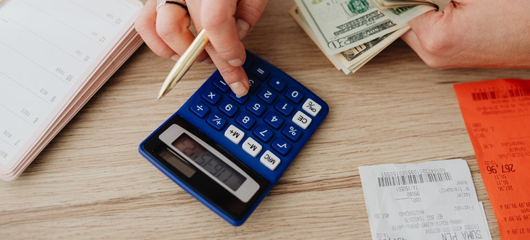 Person using a calculator to define a budget for moving from upstate NY to Brooklyn