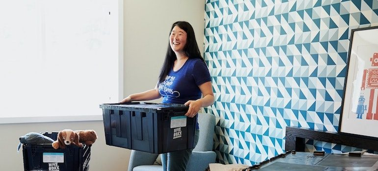 woman carrying a box in a bedroom