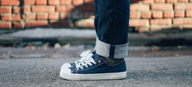two feet in sneakers standing on a street