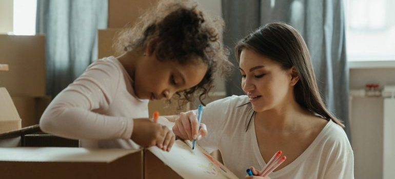 Mother and daughter drawing on a moving box