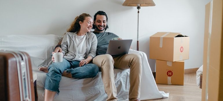 couple in a living room sitting on a sofa surrounded by boxes