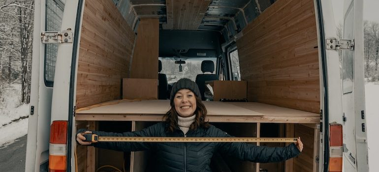 A woman with a measuring tape in front of open truck doors