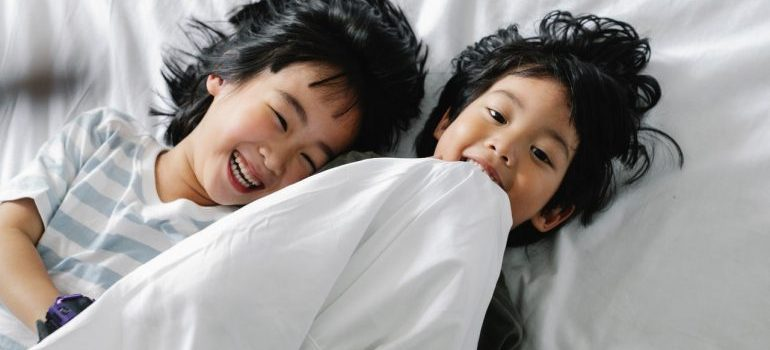 Two kids laughing in bed.