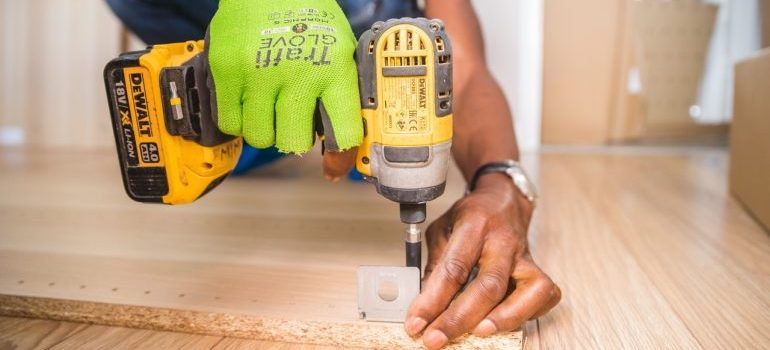 A man holding a screw and working because he is moving into an unfinished home.