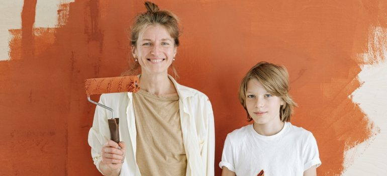 A mother and her son paining a wall.