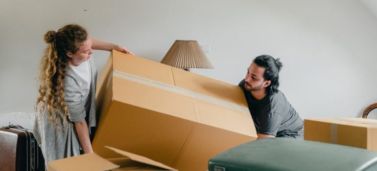 A man and a woman carrying a moving box.