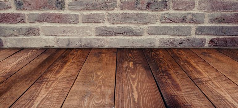 A picture of a wooden floor and a brick wall meeting.