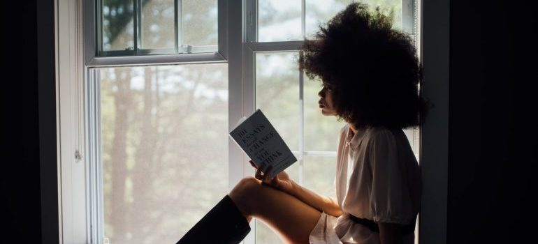 A lonely woman reading a book by a window.