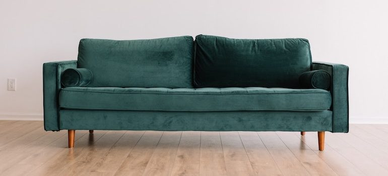 A blue-green sofa in a room with a wooden floor