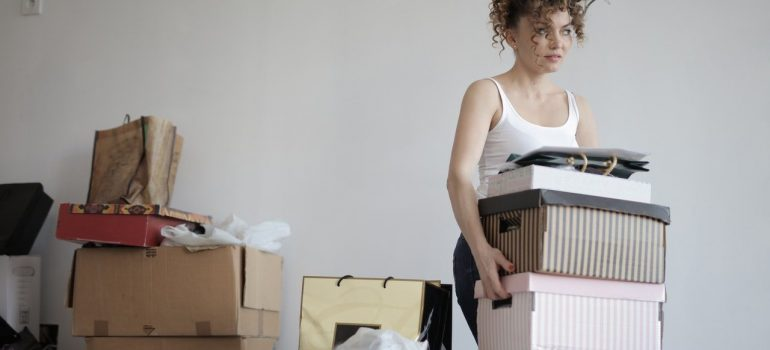 a woman carrying a couple of boxes out of a room filled with boxes