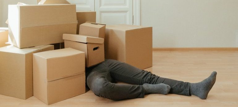 A man covered in moving boxes.