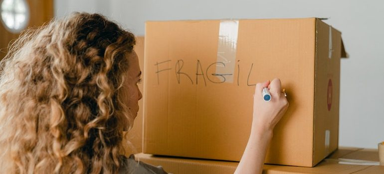 woman writing on a box sign fragile