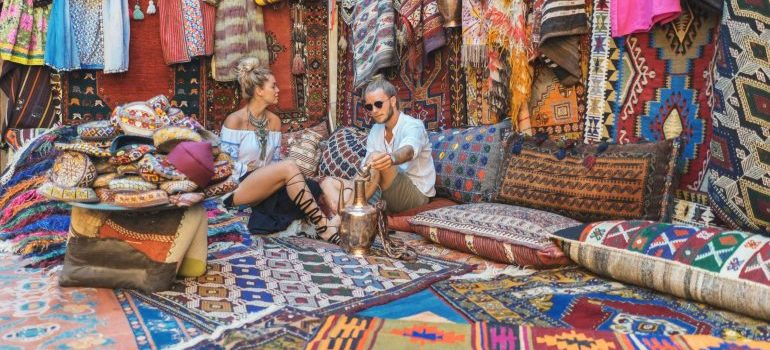 A man and a woman being surrounded by lots of colorful carpets and rugs.