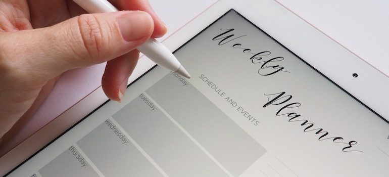 hand holding a pen over a weekly planner on a tablet