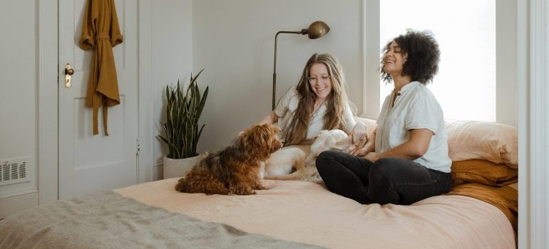 two women and a dog on a bed